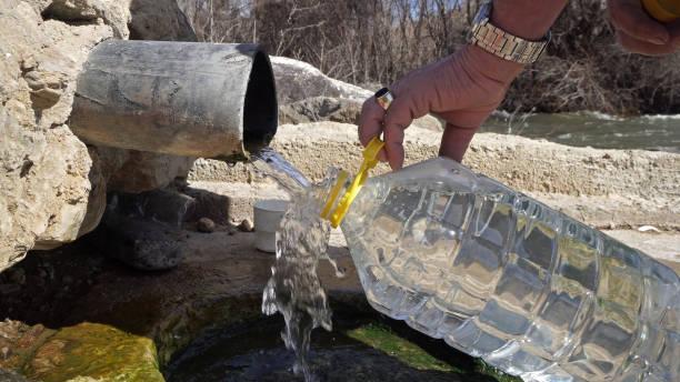 old man fill plastic bottle with thermal drink water from natural spring - tap water zdjęcia i obrazy z banku zdjęć