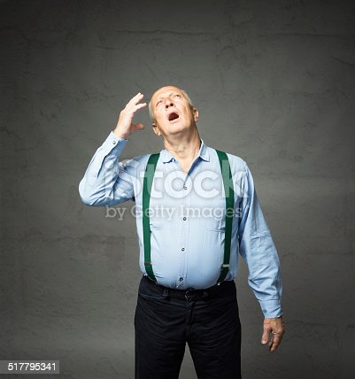862431374 istock photo old man forgetful expression on dark background 517795341