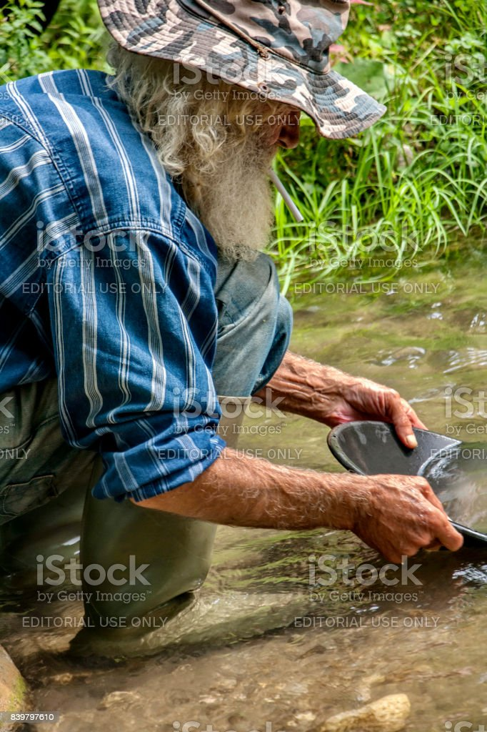 Old man gold digger washing gold in a river stock photo