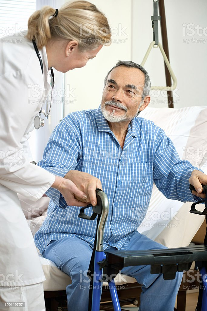 Old man helped off a hospital bed by female nurse and walker stock photo