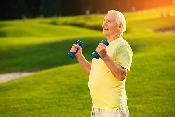 Old man holding dumbbells. - foto de stock