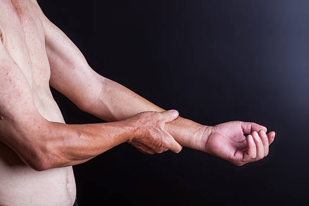 old man holding his arm with blackbackground - Photo