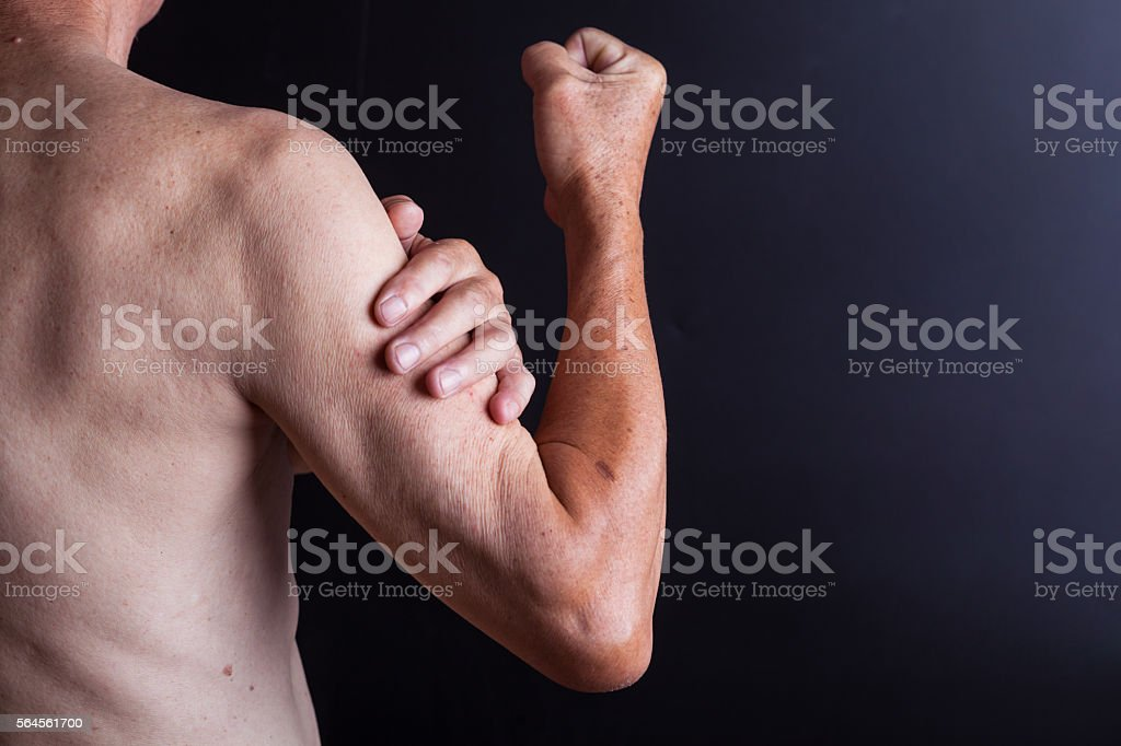 old man holding his arm with blackbackground stock photo