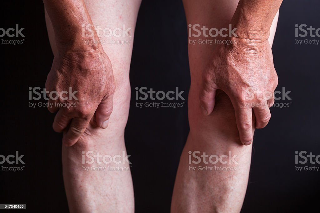 old man holding his knees with black background Lizenzfreies stock-foto