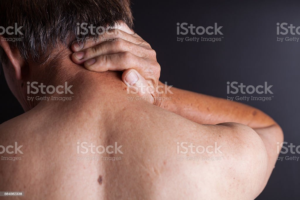 old man holding his neck with blackbackground studio shot