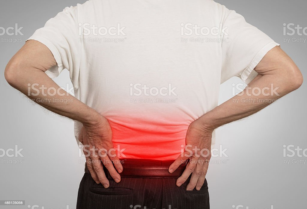 old man holding his painful lower back colored in red stock photo