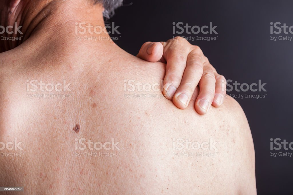 old man holding his shoulder with blackbackground stock photo