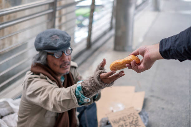 Old man homeless reach out to get bread from donor Old man homeless reach out to get bread from donor on corridor bridge stranger stock pictures, royalty-free photos & images