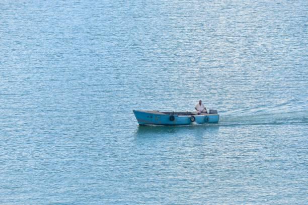 alter mann in einem motorboot - senior bilder wasser stock-fotos und bilder