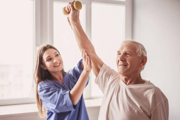 hastanedeki yaşlı adam - physical therapy stok fotoğraflar ve resimler