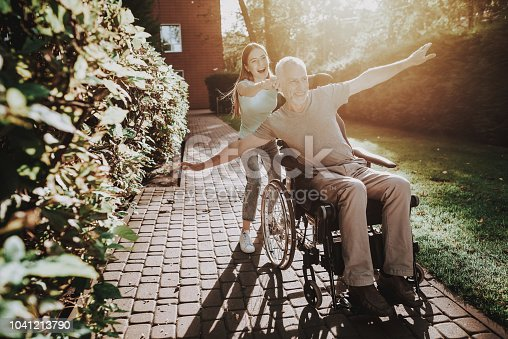 istock Old Man in Wheelchair. Happy Aged and Young Girl. 1041213790