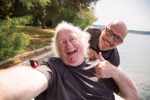 old man in wheelchair taking a selfie with his phone stock photo