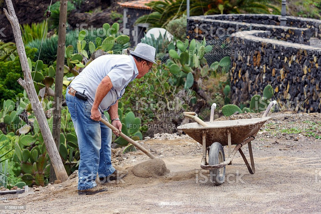 Old man is digging ground in his garden. stock photo