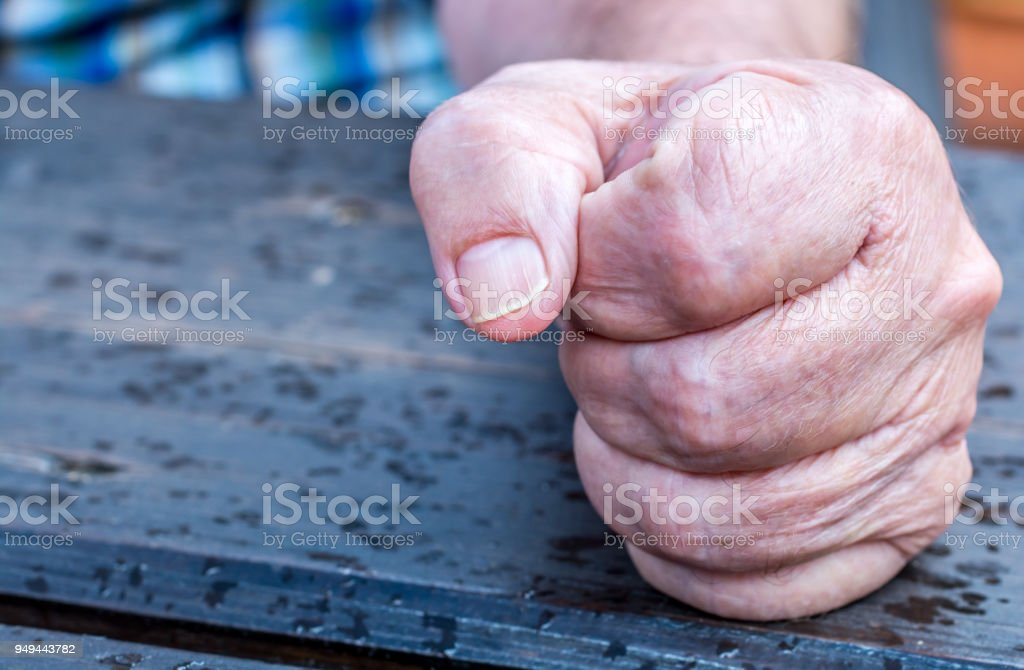Old man knocks on the table stock photo