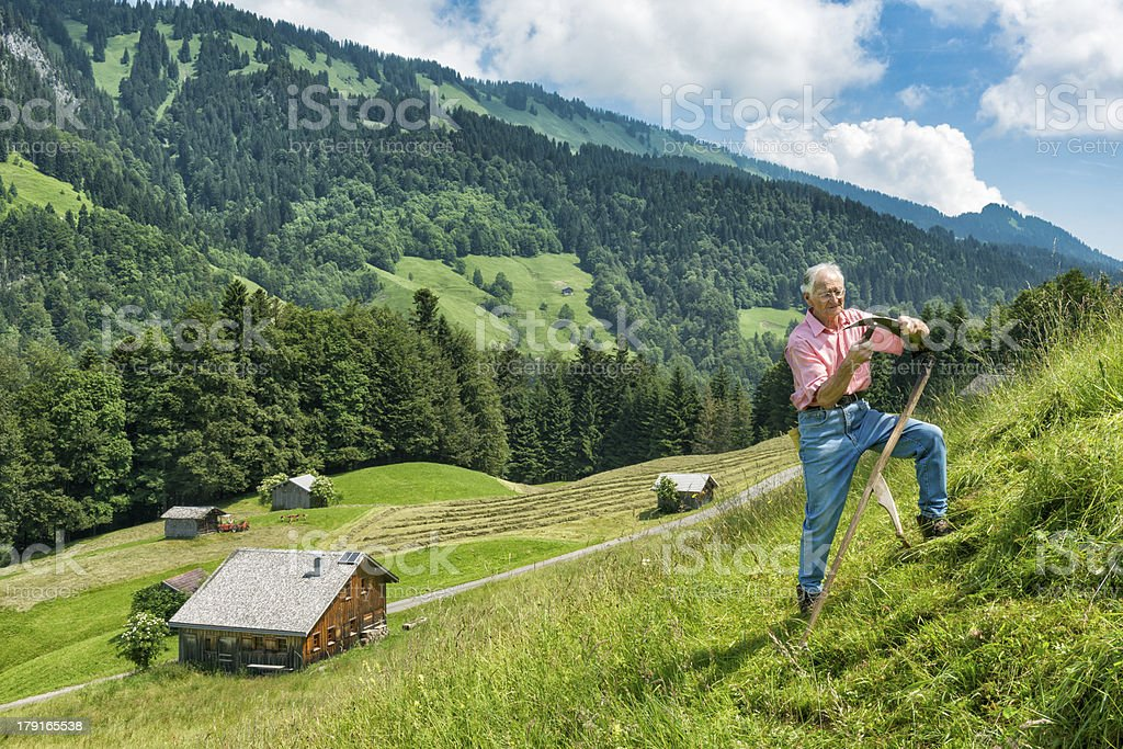 old man mowing with scythe in the mountains royalty-free stock photo
