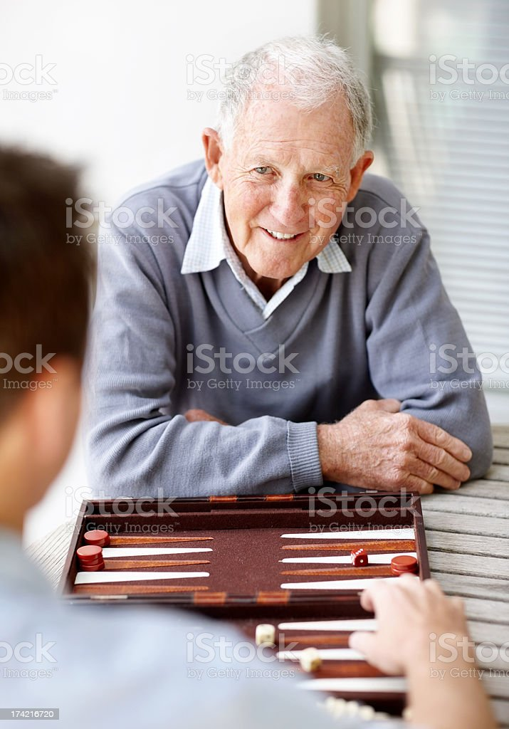 Old man playing backgammon with a young man stock photo