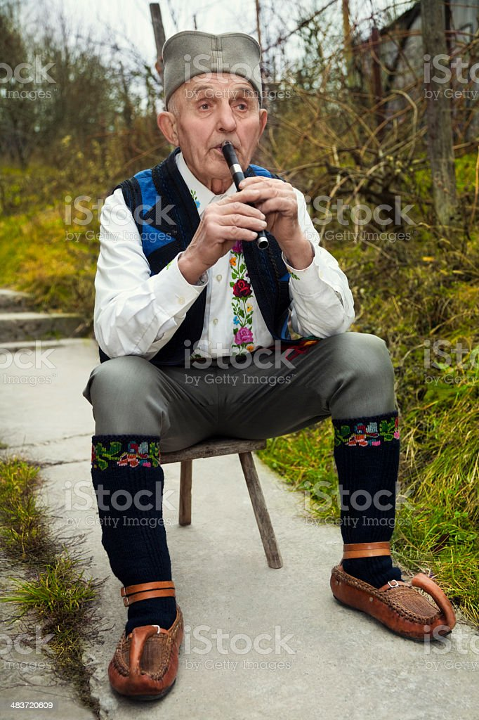 Old man playing fife royalty-free stock photo