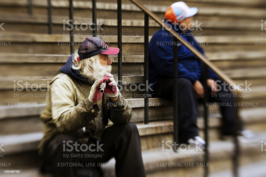 Old man playing flute in Wall Street stock photo