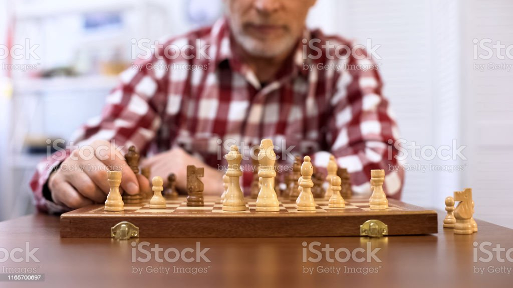 Old man playing table game, championship wooden chess set, storage of...