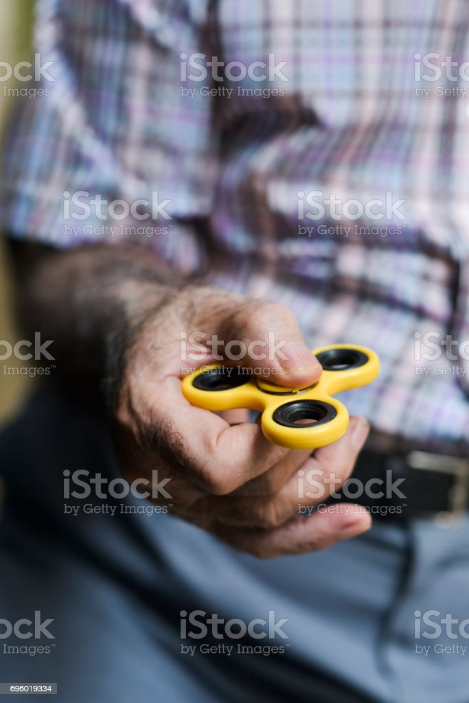old man playing with a fidget spinner stock photo