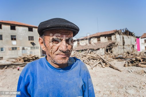 Denizli, Turkey - November 7, 2015: old man with potresi and ruined houses behind