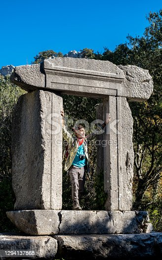 Ancient city ruins intertwined with nature. 60 years old, healthy man hiking.
