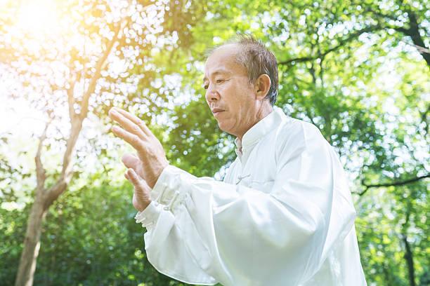old man practice tai chi in the park - foto de stock