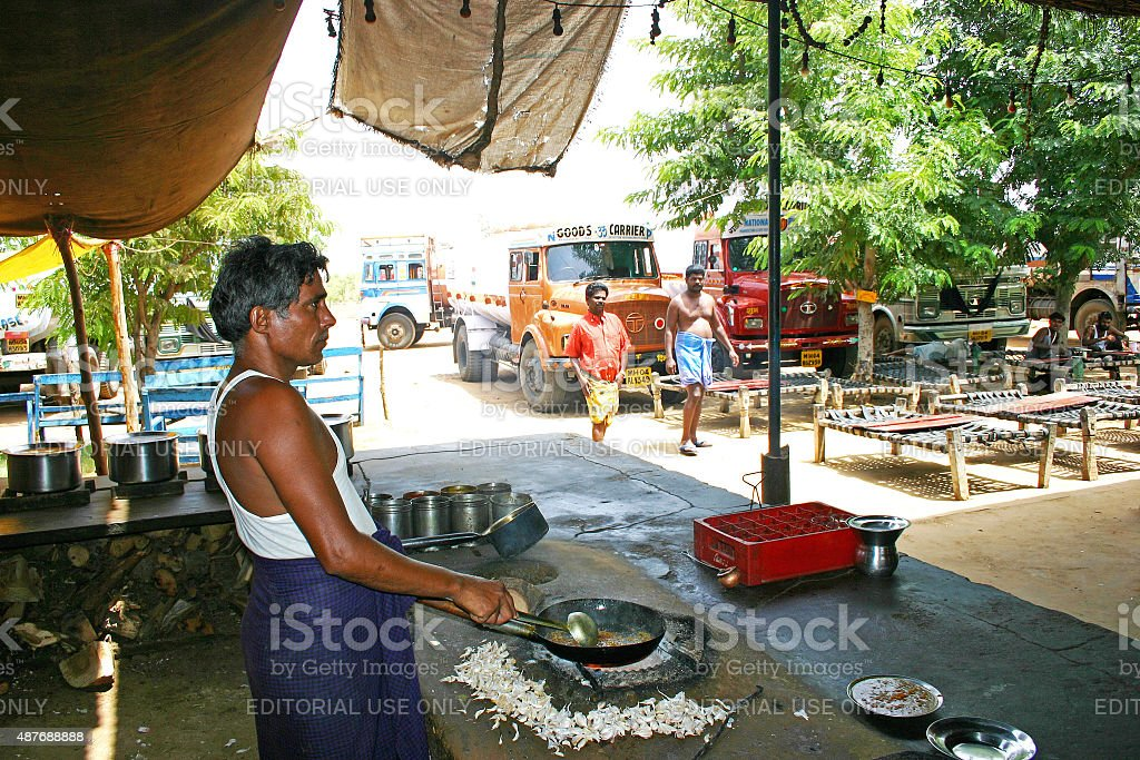 Old man preparing food on the roadside eatery place stock photo