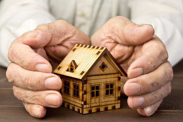 old man protecting house model with hands .risk insurance. the concept of mortgages and bank loans. poverty. rental property. - senior housing stock photos and pictures