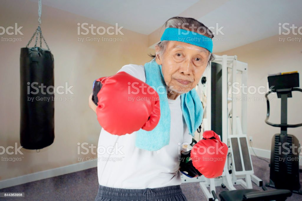 Old man punching camera in the fitness center stock photo
