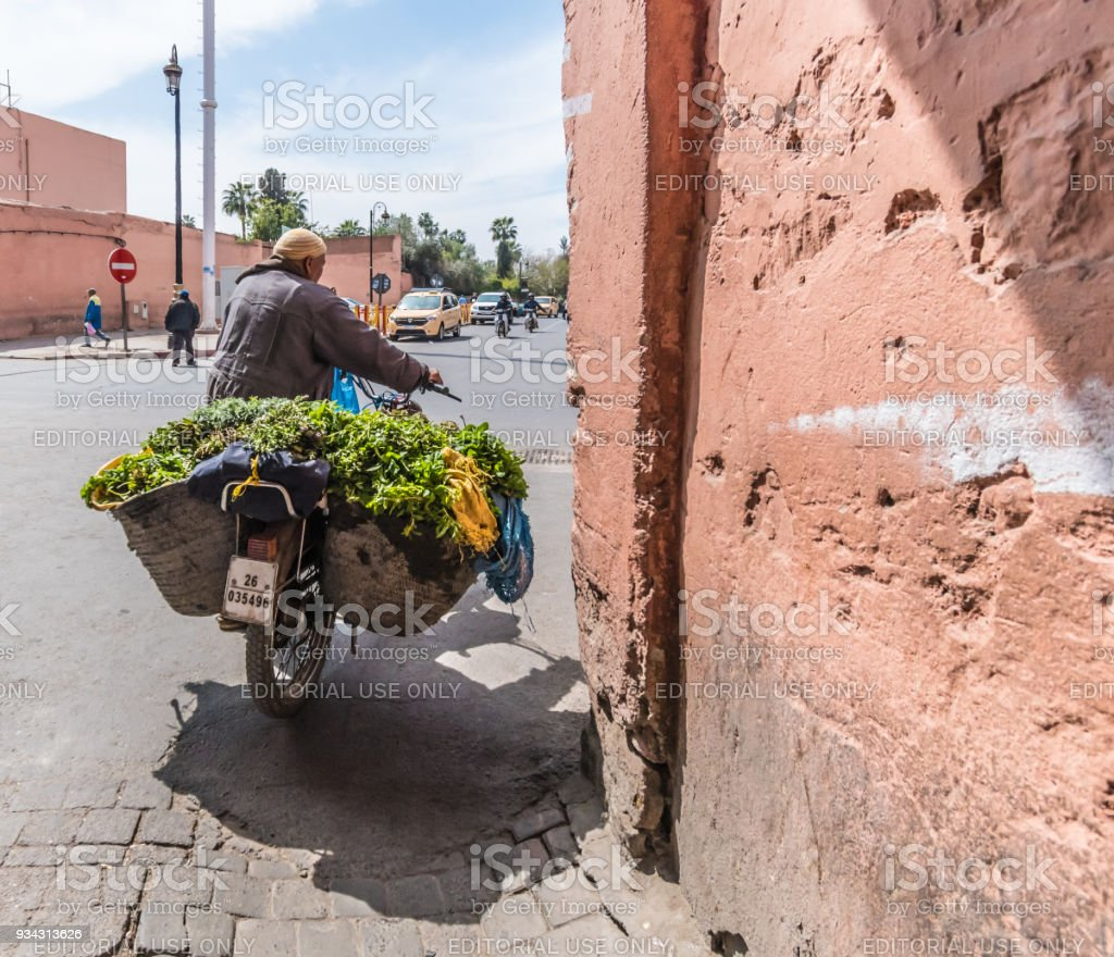 Old man pushes motorcycle laden with vegetables in Marrakesh stock photo