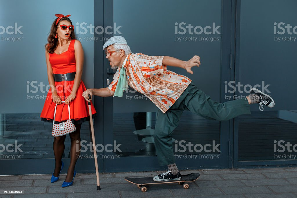 Old man quickly rides a skateboard on the street. stock photo