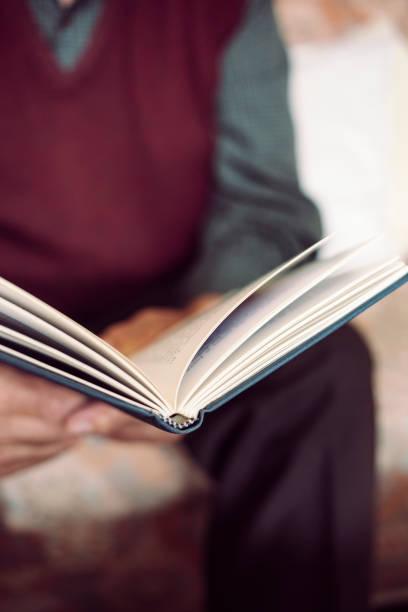 alter mann liest ein buch - gedichte zum ruhestand stock-fotos und bilder