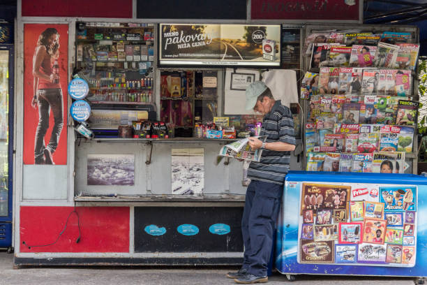 Belgrade, Serbia - August 2, 2015: Old man reading a newspaper at a kiosk (Trafika) in summer in the capital city of Serbia. These kiosks are a typical part of Balkan urbanism stock photo