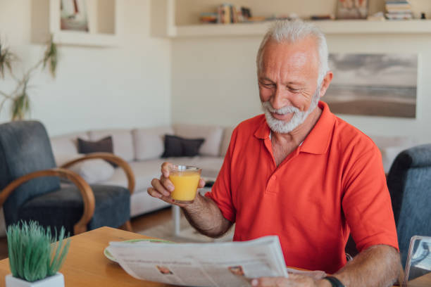 Old man reading newspapers and drinking orange juice stock photo