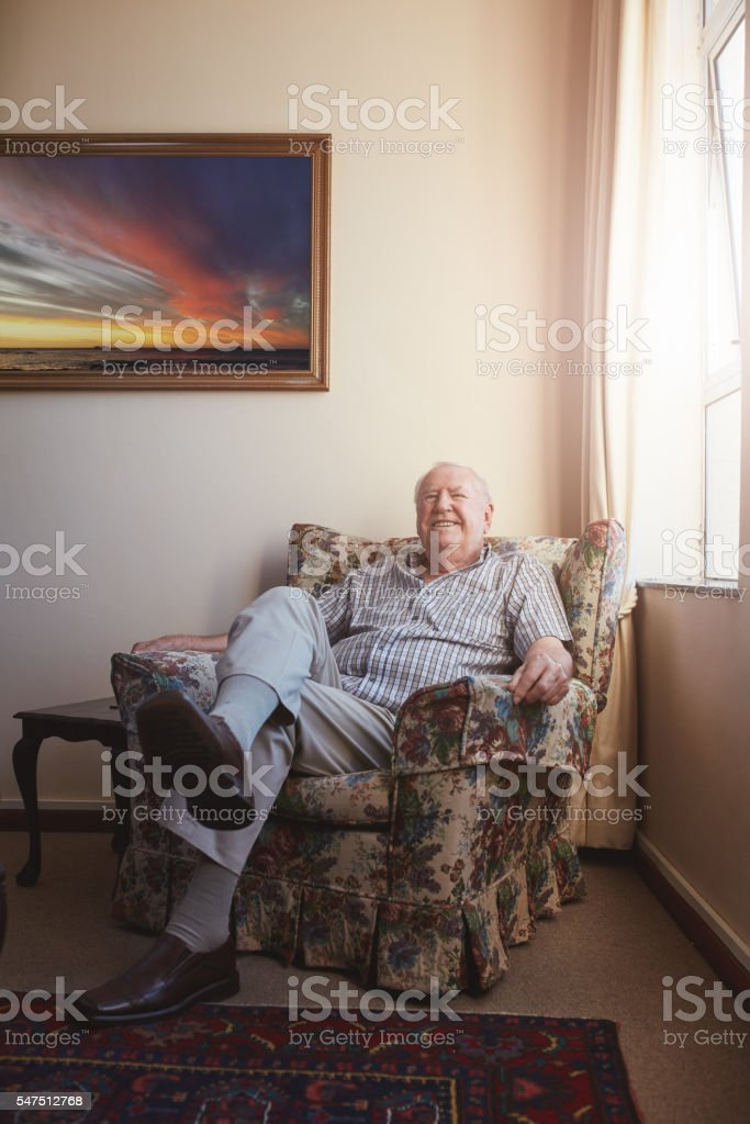 Old man relaxing on an arm chair at home stock photo