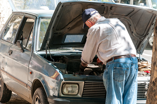 Old man repairs his broken Yugo car on the street. View from back.