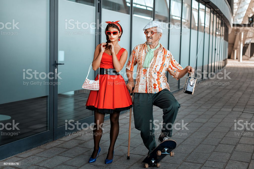 Old man saunters with a young girl. stock photo