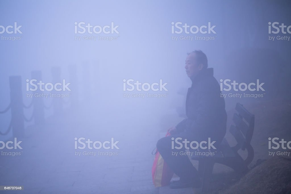 Old man seat in the mist stock photo