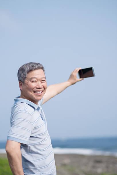 alter mann selfie und lächeln - senior bilder wasser stock-fotos und bilder