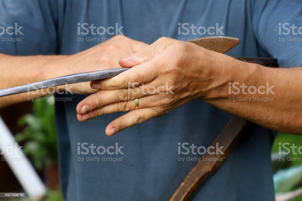 A old man sharpening steel edge of scythe with wet whetstone stock photo