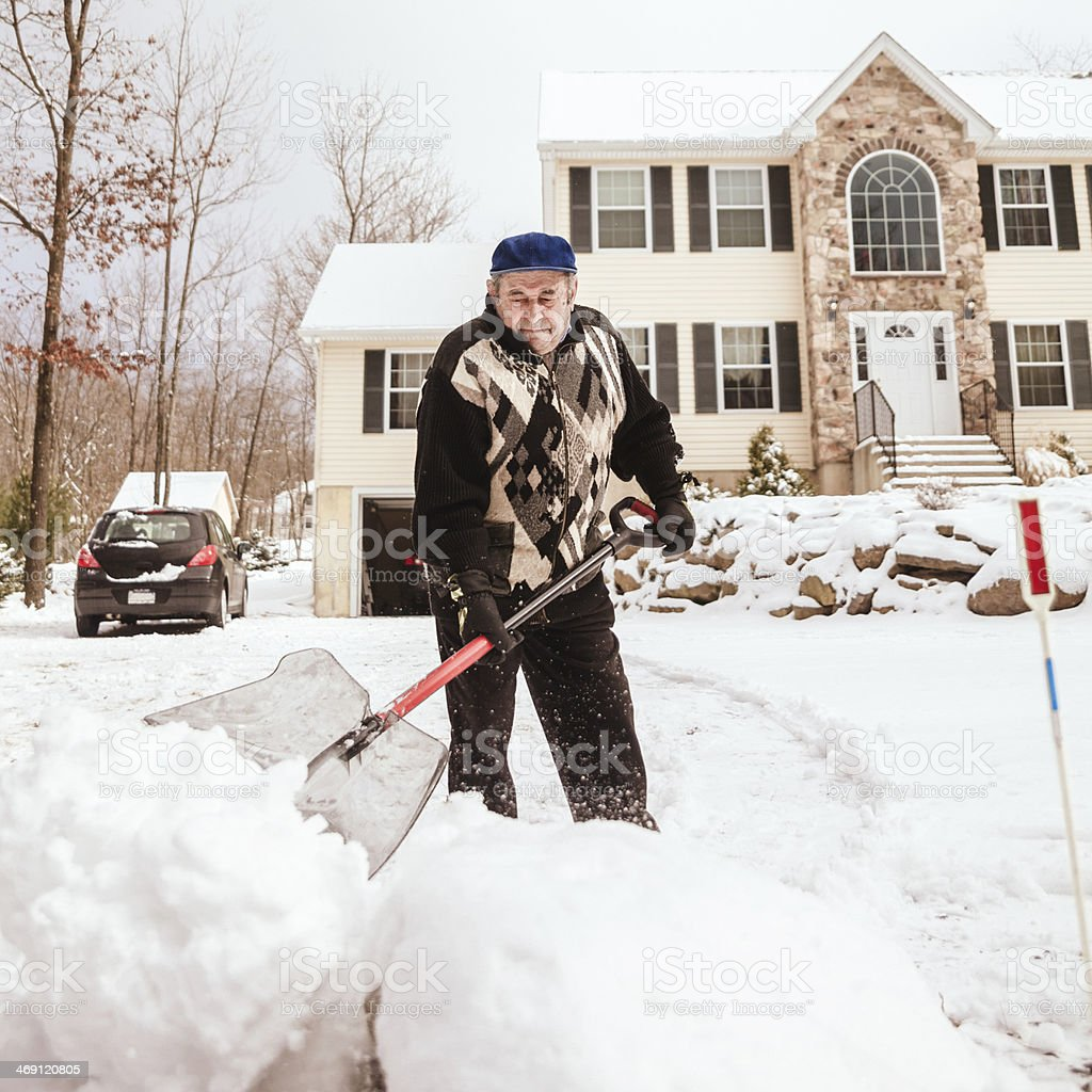 Old man shoveling a path in the snow stock photo