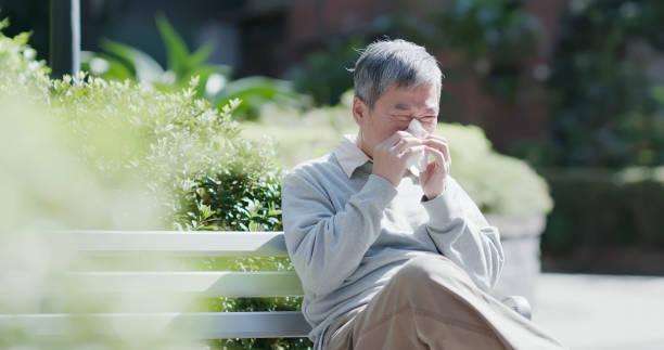 oude man ziek en niezen - allergie stockfoto's en -beelden