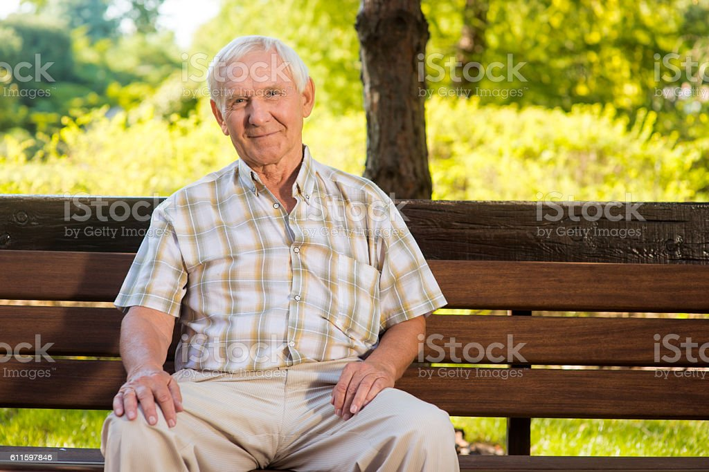 Old man sits on bench. stock photo