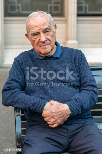Old hispanic man sitting in a city bench looking at the camera