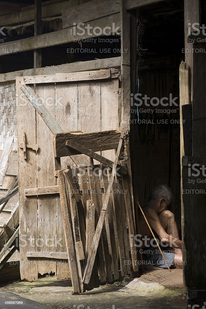 Old man sitting in the door opening of Iban Longhouse stock photo
