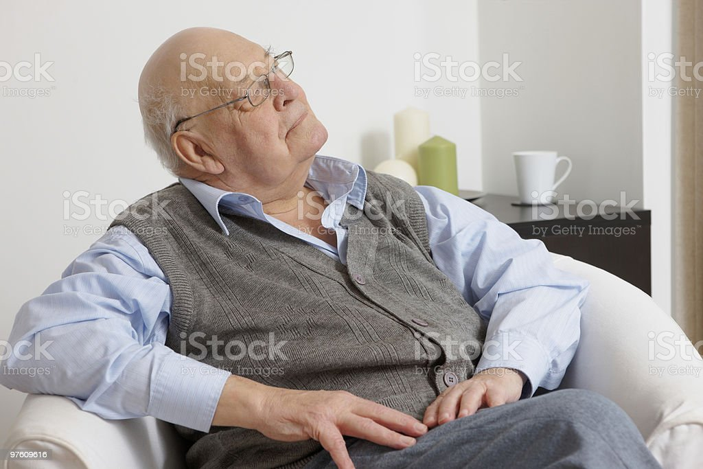 Old man sitting on sofa at home daydreaming royalty-free stock photo