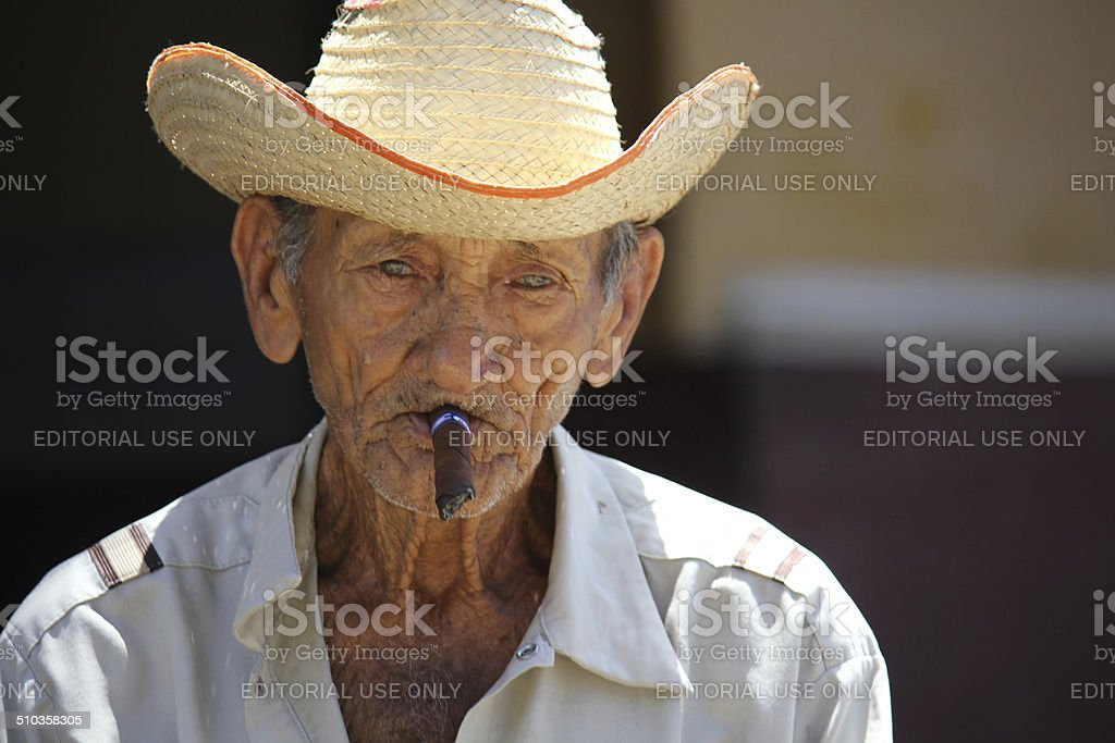 Old man smoking a cigar. stock photo