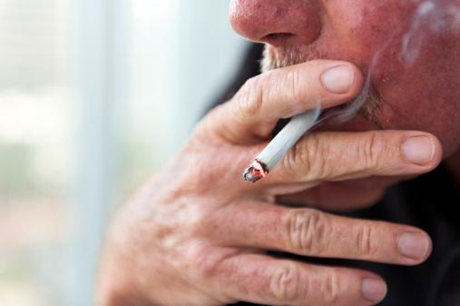Caucasian old man smoking a cigarette