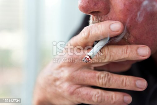 Caucasian old man smoking a cigarette